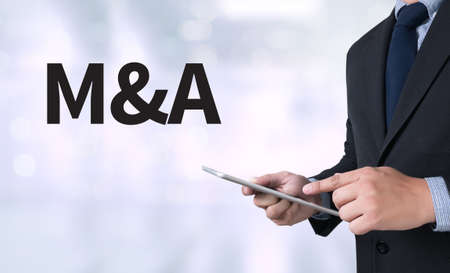 mergers: M&A (MERGERS AND ACQUISITIONS) Businessman use a tablet computer Stock Photo