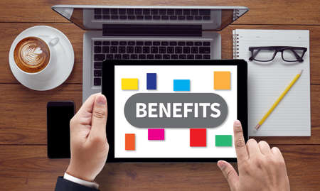 additional compensation: BENEFITS, on the tablet pc screen held by businessman hands - online, top view