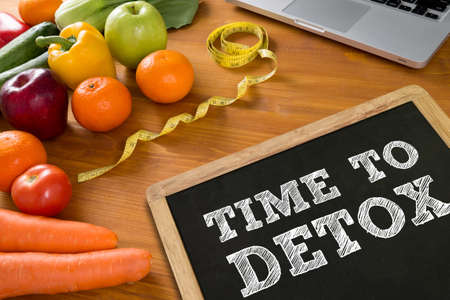 TIME TO DETOX Fitness and weight loss concept, fruit and tape measure on a wooden table, top view