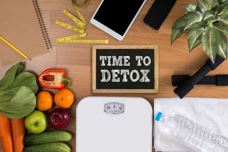 TIME TO DETOX top view, fitness and weight loss concept, dumbbells, white scale, towels, fruit, Blank board copy space