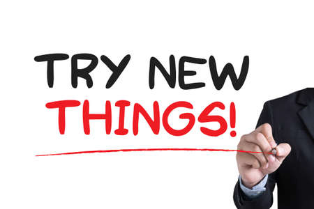 in need of space: TRY NEW THINGS Businessman hand writing with black marker on white background Stock Photo