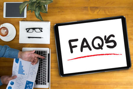 faqs: FAQs Frequently Asked Questions  Businessman working at office desk and using computer and objects, coffee, top view,