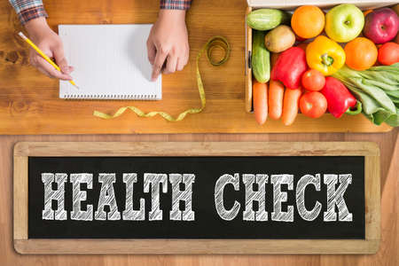 HEALTH CHECK  fresh vegetables and  on a wooden table