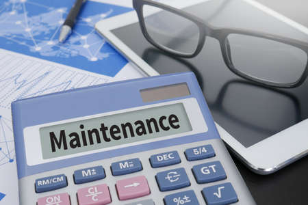 scheduled replacement: Maintenance Calculator  on table with Office Supplies. Stock Photo