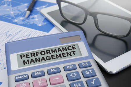 overruns: PERFORMANCE MANAGEMENT Calculator  on table with Office Supplies. Stock Photo
