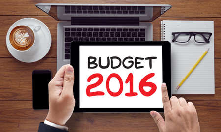 BUDGET 2016, on the tablet pc screen held by businessman hands - online, top view