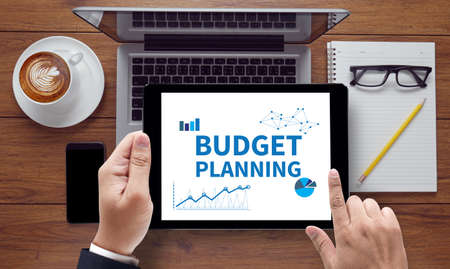 bankroll: BUDGET PLANNING, on the tablet pc screen held by businessman hands - online, top view Stock Photo