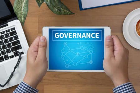 gov: GOVERNANCE man hand Tablet and coffee cup Stock Photo