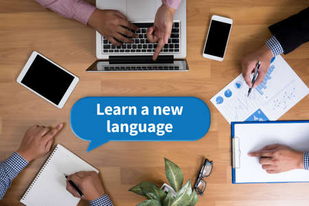 fluency: Learn a new language Business team hands at work with financial reports and a laptop, top view