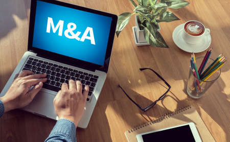 mergers: M&A (MERGERS AND ACQUISITIONS) man hand on table Business, coffee, Split tone
