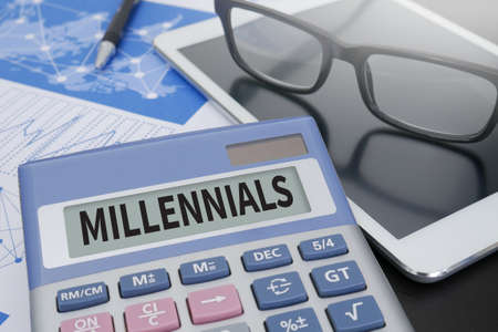 generational: MILLENNIALS  Calculator  on table with Office Supplies. ipad Stock Photo