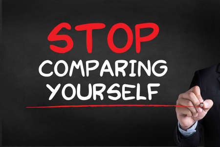 comparing: STOP COMPARING YOURSELF Businessman drawing Landing Page on blackground