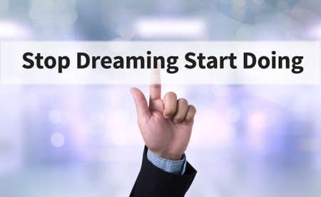 doing business: Stop Dreaming Start Doing Business man with hand pressing a button on blurred abstract background Stock Photo