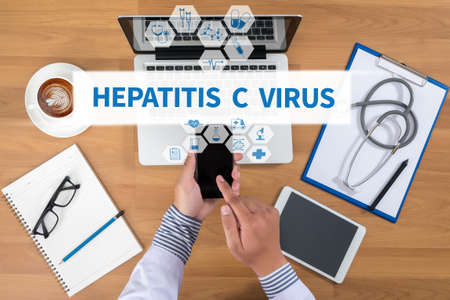 genotype: HEPATITIS C VIRUS Doctor working at office desk and using a mobile touch screen phone, computer and medical equipment all around, top view, coffee