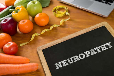 involuntary: NEUROPATHY Fitness and weight loss concept, fruit and tape measure on a wooden table, top view