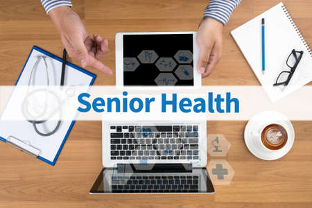 disease cure: Senior Health Doctor touch digital tablet, desktop with medical equipment on background, top view, coffee