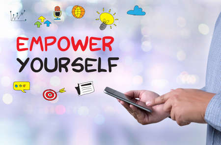 empower: EMPOWER YOURSELF person holding a smartphone on blurred cityscape background Stock Photo