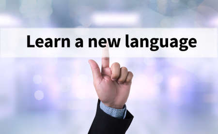 fluency: Learn a new language Business man with hand pressing a button on blurred abstract background Stock Photo