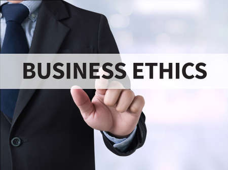 business ethics: BUSINESS ETHICS Businessman touching a touch screen on blurred city background Stock Photo