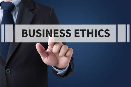 business ethics: BUSINESS ETHICS Businessman hands touching on virtual screen and blurred city background