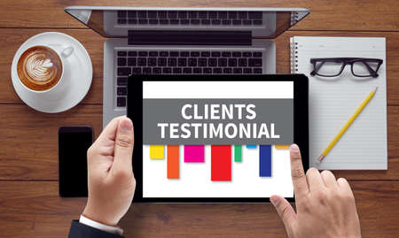 affirmations: CLIENT TESTIMONIAIS, on the tablet pc screen held by businessman hands - online, top view