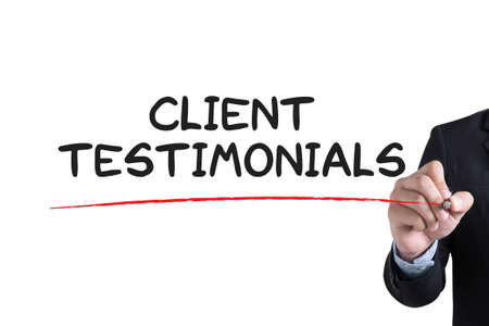 affirmations: CLIENT TESTIMONIALS Businessman hand writing with black marker on white background Stock Photo