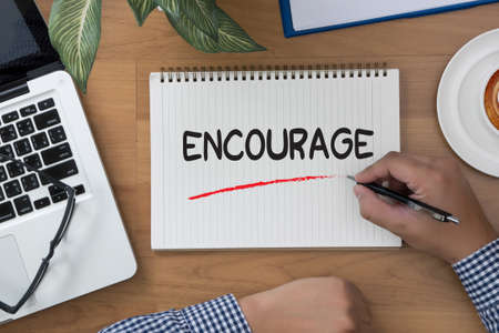encourage: ENCOURAGE man hand notebook and other office equipment such as computer keyboard Stock Photo