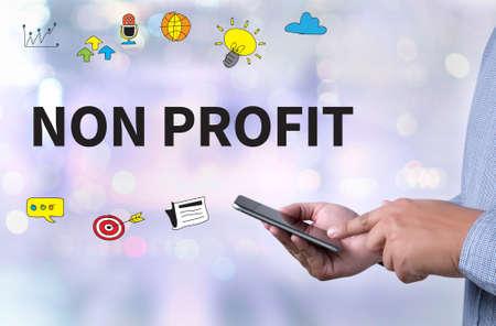 non profit: NON PROFIT person holding a smartphone on blurred cityscape background Stock Photo