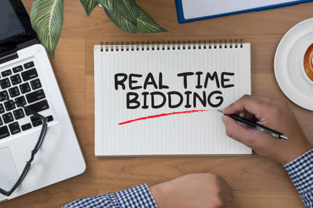 bidding: REAL TIME BIDDING man hand notebook and other office equipment such as computer keyboard Stock Photo