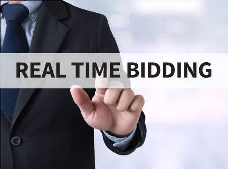 bidding: REAL TIME BIDDING Businessman touching a touch screen on blurred city background Stock Photo