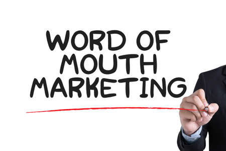 referrer: WORD OF MOUTH MARKETING Businessman hand writing with black marker on white background