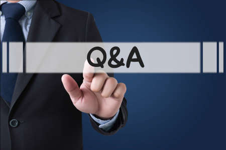qa: Q&A - Question and Answer Businessman hands touching on virtual screen and blurred city background
