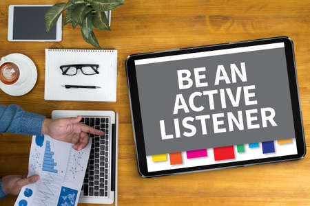 listener: BE AN ACTIVE LISTENER Businessman working at office desk and using computer and objects, coffee, top view,