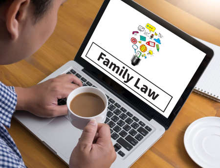maternity leave: Family Law  Businessman at work. Close-up top view of man working on laptop while sitting at the wooden desk , coffee