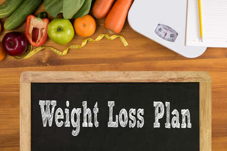 weight loss plan: weight loss plan Fitness and weight loss concept, dumbbells, white scale, fruit and tape measure on a wooden table, top view, free copy space