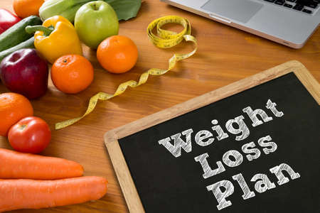 weight loss plan: weight loss plan Fitness and weight loss concept, fruit and tape measure on a wooden table, top view