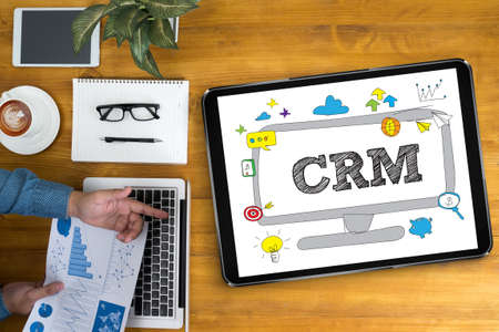 interactions: CRM  Business Customer CRM Management Analysis Service Concept  Businessman working at office desk and using computer and objects, coffee, top view,