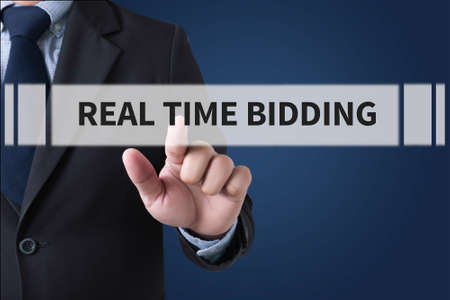bidding: REAL TIME BIDDING Businessman hands touching on virtual screen and blurred city background Stock Photo