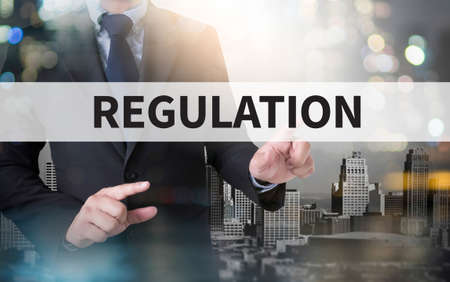 government regulations: REGULATION and businessman working with modern technology Stock Photo