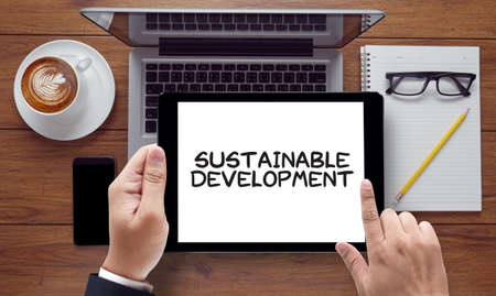 economic theory: SUSTAINABLE DEVELOPMENT, on the tablet pc screen held by businessman hands - online, top view