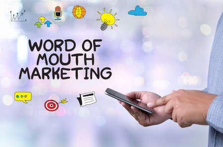 referrer: WORD OF MOUTH MARKETING person holding a smartphone on blurred cityscape background