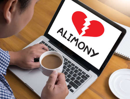alimony: Alimony Businessman at work. Close-up top view of man working on laptop while sitting at the wooden desk , coffee