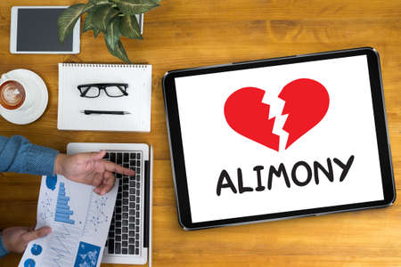 alimony: Alimony Businessman working at office desk and using computer and objects, coffee, top view,