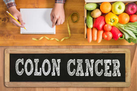 COLON CANCER fresh vegetables and  on a wooden table
