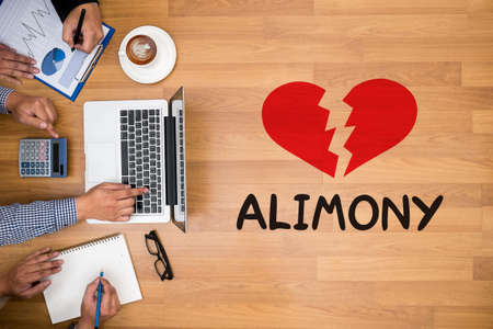 alimony: Alimony Business team hands at work with financial reports and a laptop