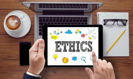 respecting: ETHICS, on the tablet pc screen held by businessman hands - online, top view Stock Photo