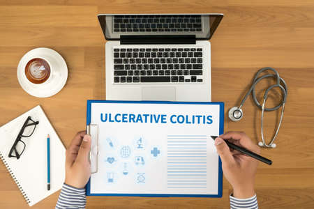 colorectal cancer: ULCERATIVE COLITIS Doctor writing medical records on a clipboard, medical equipment and desktop on background, top view, coffee Stock Photo