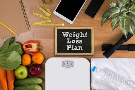 weight loss plan: weight loss plan top view, fitness and weight loss concept, dumbbells, white scale, towels, fruit, Blank board copy space Stock Photo