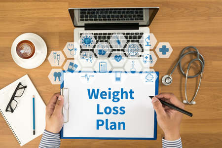 weight loss plan: weight loss plan Top view, Doctor writing medical records on a clipboard, medical equipment Stock Photo