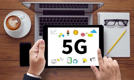 5g: 5G, on the tablet pc screen held by businessman hands - online, top view Stock Photo